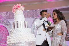 Indian bride tasting the wedding cake