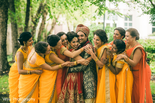 Indian bridesmaids holding the couple