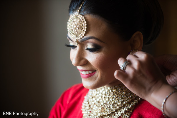 Indian bride putting earrings on