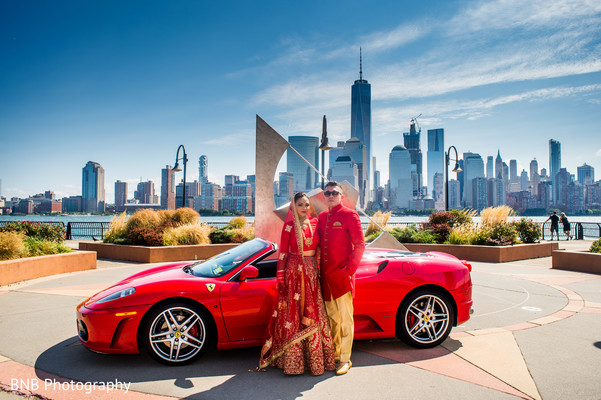Indian bride and groom next to luxury wedding car