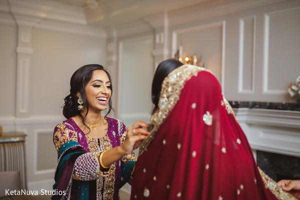Enchanting bridesmaid helping the bride get ready.
