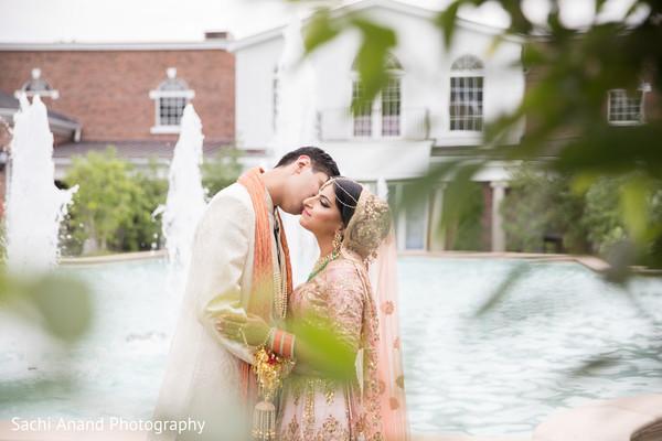 Sweet indian groom kissing bride's cheek