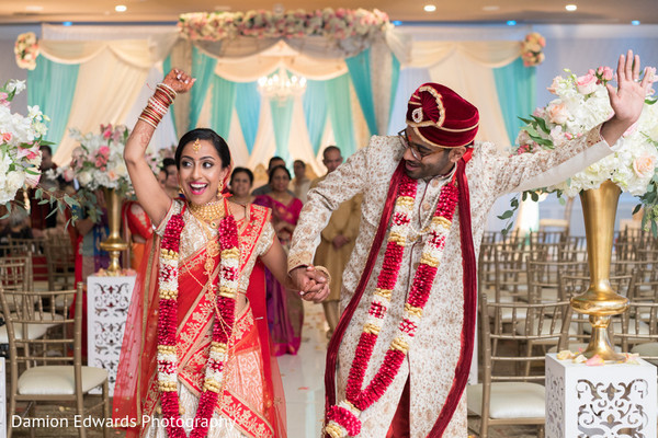 Joyful indian couple leaving wedding ritual