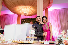 Charming indian couple posing with wedding cake