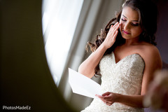 Adorable indian bride reading letter from groom