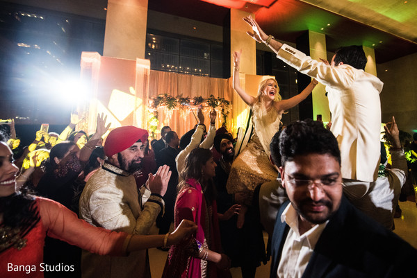 Indian couple being lifted up during sangeet