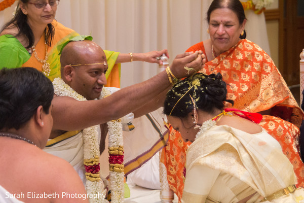 Indian bride being showered with rice by the groom.