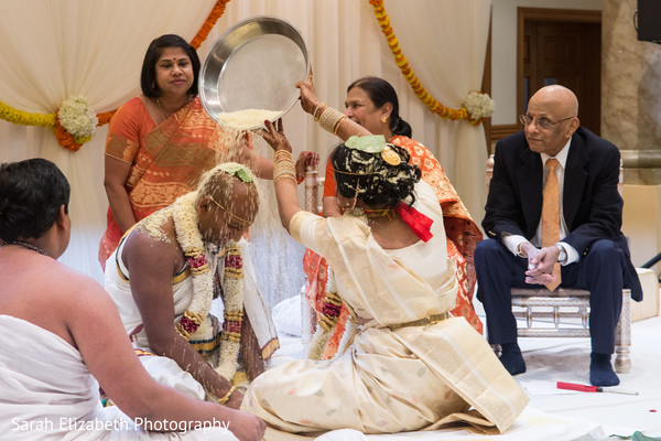 Indian groom being showered with rice by the bride.