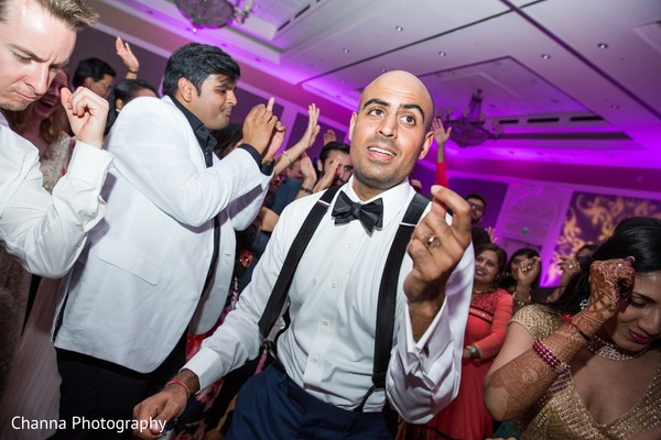 Indian groom dancing during reception party