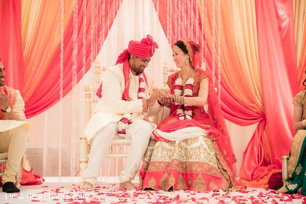 Indian groom putting wedding ring on bride
