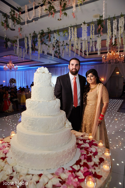 Indian bride and groom posing with wedding cake