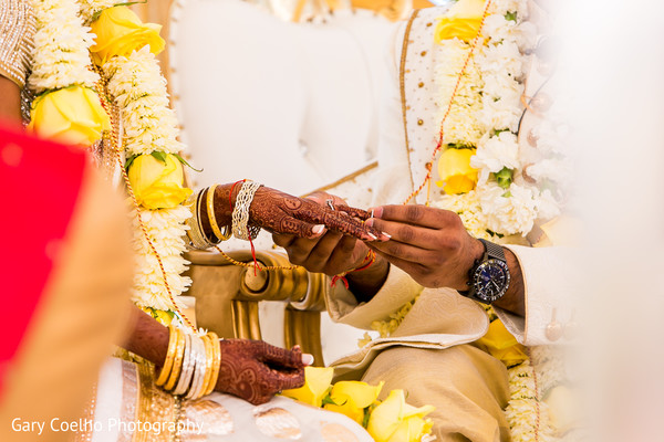 Indian groom putting wedding ring on bride