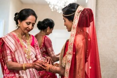 Indian bride's mother helping her to get ready