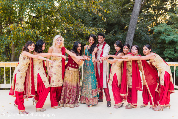 Joyful indian bride and groom with bridesmaids capture