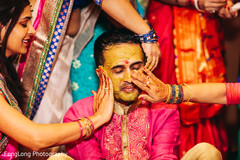 Indian wedding ritual of painting the groom with yellow turmeric paste