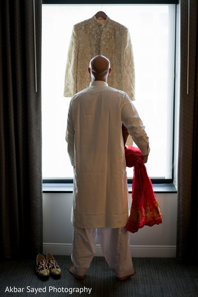 Charming indian groom looking at wedding outfit