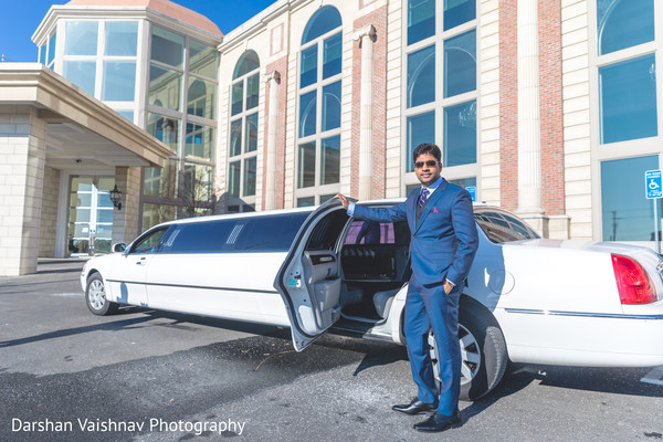 Enchanting indian groom posing with limo