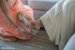 Lovely indian bride being helped with shoes
