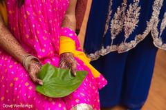 Indian bride's hands holding betel leaf close up