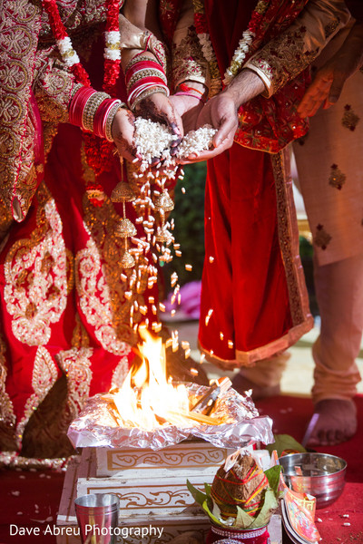 Indian bride and groom making offerings to sacred fire