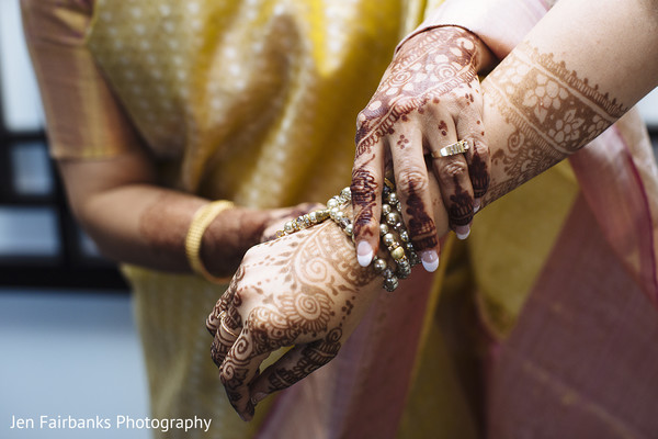 Indian bride being helped with jewelry