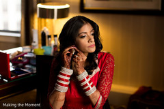 Beautiful indian bride putting earrings on