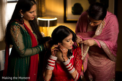 Sweet indian bride being helped with jewelry