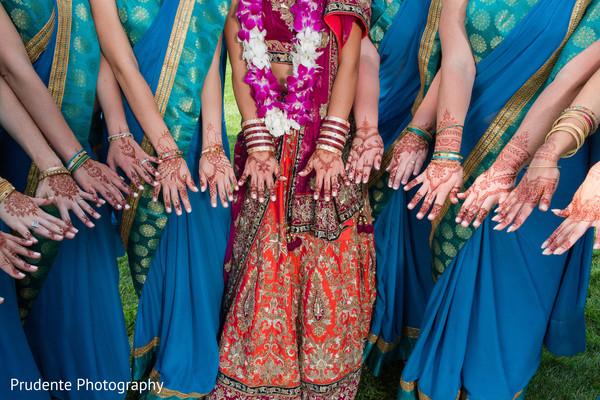 Indian bride with bridesmaids showing mehndi art