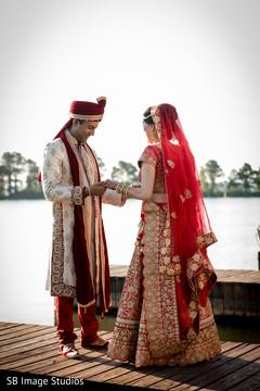 Indian groom admiring bridal mehndi art