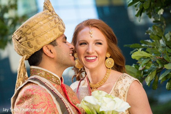 Indian groom kissing the bride to be