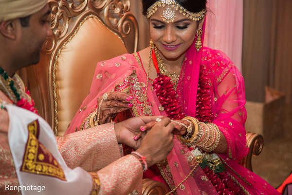 Indian groom placing wedding ring to bride during wedding ceremony.
