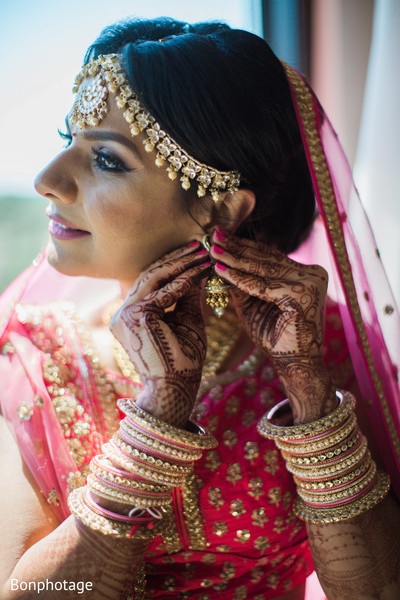 Gorgeous Indian bride putting her ceremony Jewelry.