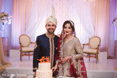 Indian lovebirds posing with wedding cake