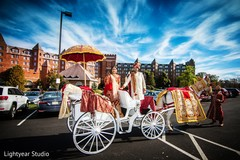 Lovely indian couple posing with wedding carriage