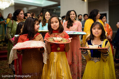 Little lovely Indian bridesmaids caring the ritual accessories.