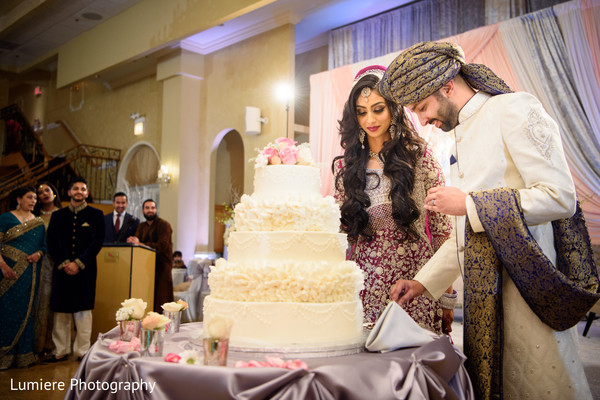 Indian bride and groom cutting their lovely wedding cake.