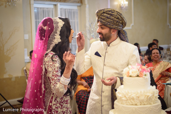 Indian groom giving the bride cake.