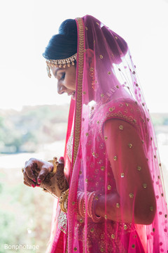 Beautiful bride with a golden pink Ghoonghat.