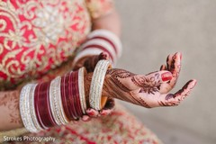 Indian bride putting bangles on