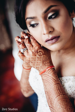 Lovely indian bride putting earrings on