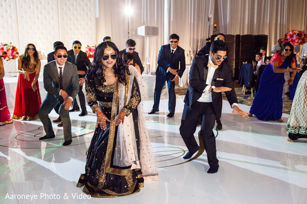 Indian bride and groom dancing along with the guests