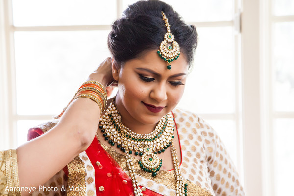 Indian bride putting on her kundan jewelry