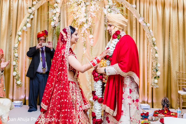 Indian bride and groom exchanging garlands ceremony.