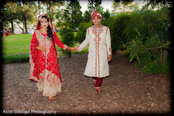 Indian bride and groom walking holding hands