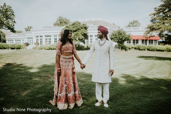Lovely Indian couple walking outdoors on their wedding traditional outfits.