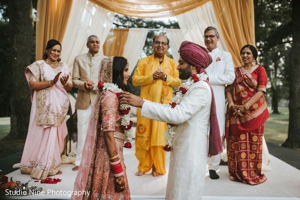 Indian groom putting flower garland to bride.