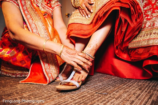 Indian bride being helped with shoes