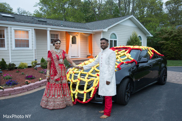 Ravishing indian couple posing with wedding car