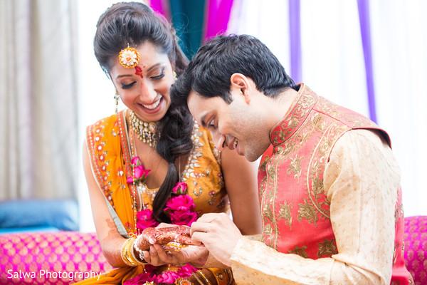 Indian groom admiring the brides mehndi art.