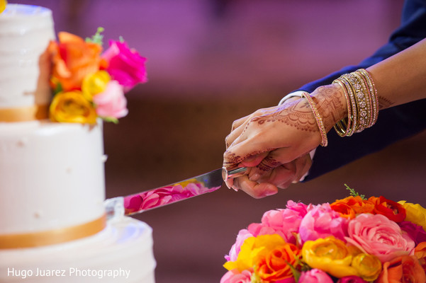India bride and groom cutting wedding cake's capture.